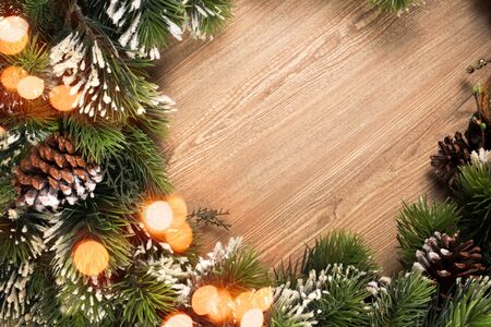 Christmas tree branch wreath with blue and green baubles and golden defocused lights on wooden background