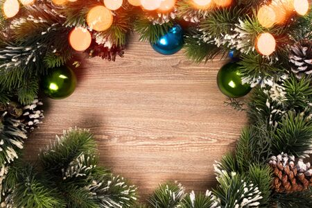 Christmas tree branch wreath with blue and green baubles and yellow lights bokeh and wooden background