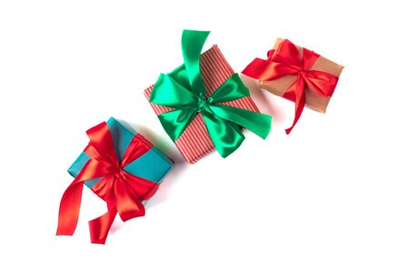 Bright christmas gifts with colorful atlas ribbons isolated on white