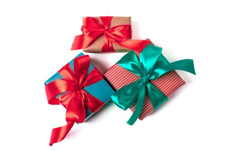 Three natural paper wrapped gift boxes with atlas ribbon bows of traditional colours, isolated on white Stok Fotoğraf