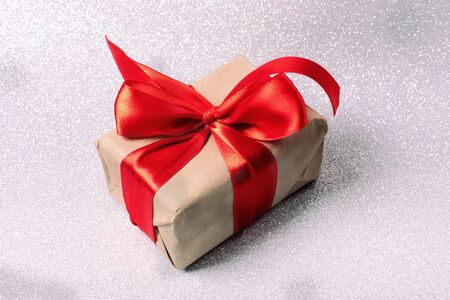 Natural eco paper wrap present with red shiny ribbon with bow on silver glitter background