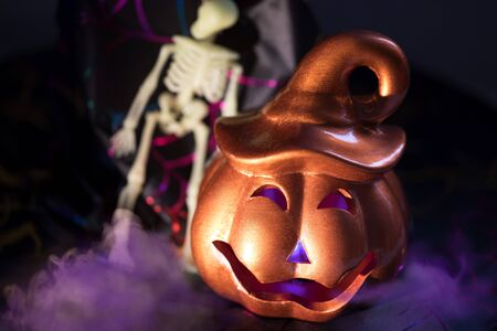 Helloween glowing evil jack-o-lantern pumpkin with sceleton and violet smog