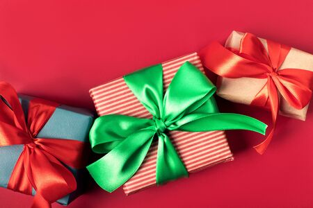 Three bright christmas gifts with colorful atlas ribbons on solid red background Stok Fotoğraf