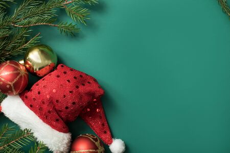 , Christmas composition of santa claus hat with baubles and tree branches on green background, festive concept