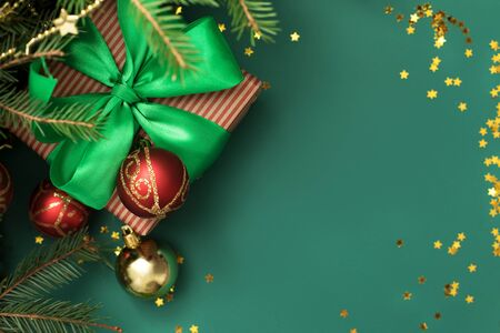Bright christmas gift with colorful traditional color atlas ribbon and bow with glass baubles under the christmas tree on solid green background with little golden stars.... Stok Fotoğraf
