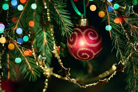 Christmas red bauble on tree with bokeh lights and golden chain