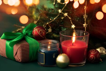 Festive christmas burning candles ubder the tree with gift box and baubles
