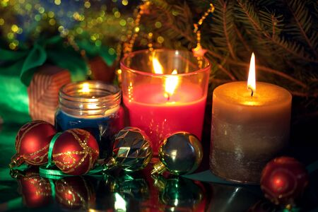 Festive christmas burning candles ubder the evegreen tree with gift box wrapped in natural paper with atlas bow and baubles aside, blur bokeh Stok Fotoğraf