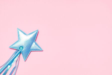 Blue sparkling fairy stick on solid pink background