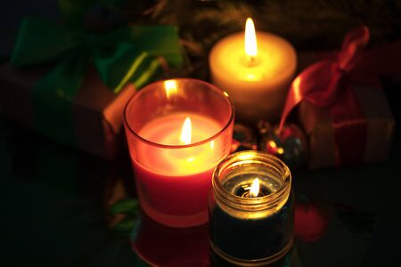 Festive christmas burning candles under the tree with gift boxes Stockfoto
