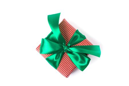 Natural paper wrapped gift boxes with atlas green bow of traditional colours, isolated on white