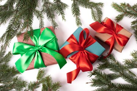 Bright christmas gifts with colorful atlas ribbon and christmas tree branches on white background
