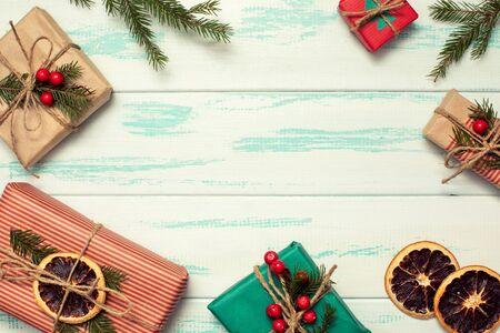 Fondo de Navidad con cajas de regalo decoradas con materiales naturales sobre fondo de madera clara. Preparativos de vacaciones, marco con espacio para texto