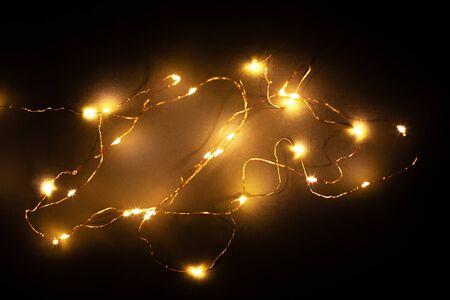 Abstrakte Weihnachts-LED-Leuchten auf schwarzem Hintergrund. Verschwommen leuchtende Glühbirnengirlande, schwarze Schicht für Bildschirmmodus-Overlays, um die Glühbirnen zu beleuchten. Festliches Konzept