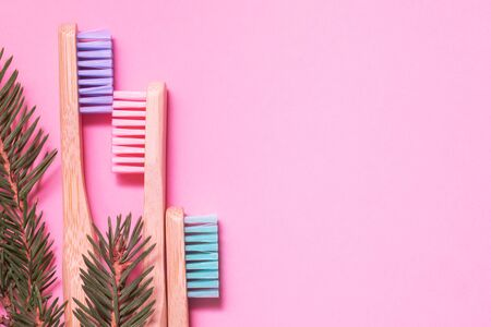 Colorful natural bamboo brushes on pink background