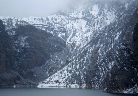 Snow covered mountain gorge with a lake at the foot.