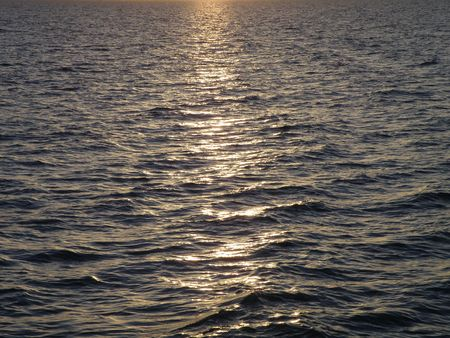 Ocean water reflects light from a sunset across the wave crests.