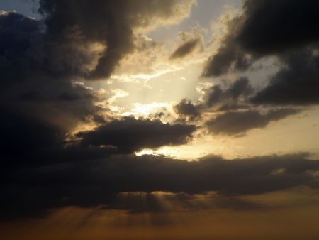 A beautiful sunset with rays of light fanning out from behind the clouds.