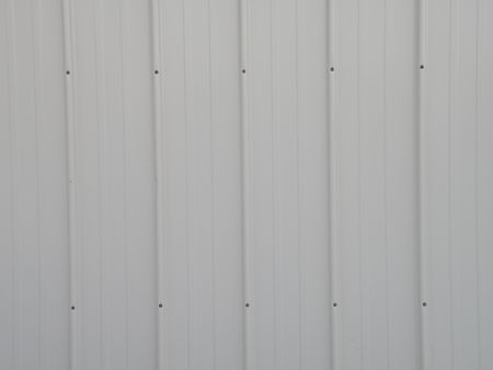 Textured background image of sheet metal siding. White with black nails and rubber washers. Stock Photo