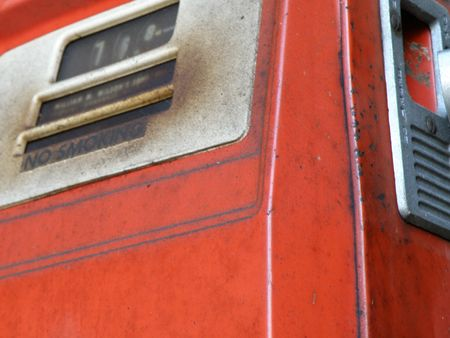 An old red gas pump with corroded and oxidized metal appearing through the original paint.