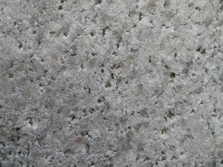A porous rock surface with colored granite qualities. Stock Photo