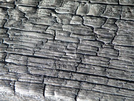 Wooden board that has been burnt black. Charred wooden surface and texture. Stock Photo