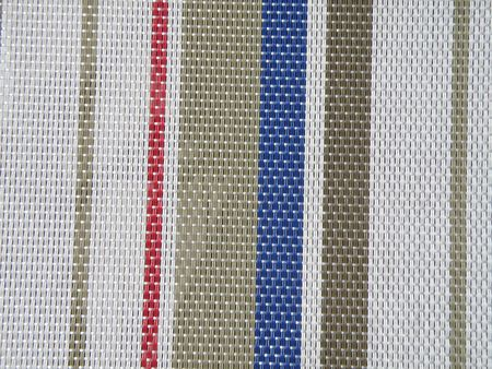 Back seat of a lawn or yard chair. Detailed woven pattern with multiple colors. Textured background.