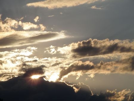 Sun falls behind dense clouds just before sunset.        Stock Photo