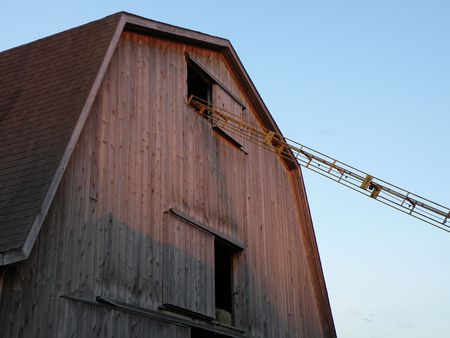 Hay elevator extends into the top portion of a large barn as the setting sun casts shadows.