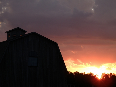 A large barn silhouette stands out in front of a bright setting sun.