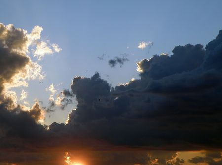 Sun falls behind dense clouds just before sunset. Blue skies lay calm above an incoming cloud formation. Фото со стока