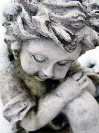 Snow covered statue of a young girl.