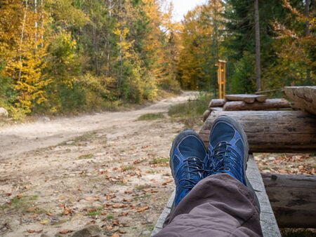 Clouse-up a man feet in blue boots while resting on the wooden bench after hiking near road and autumn forest