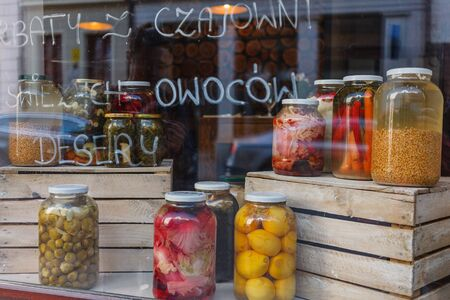Preserved vegetables in glass jars, pickles standing on the wooden boxes