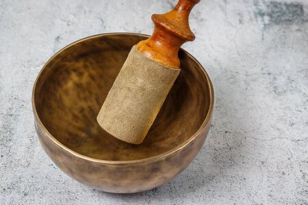 Tibetian old metal singing bowl with stick standing on the concrete background. Health, healing and meditation concept