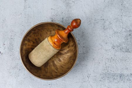 Flat lay of the Tibetian old metal singing bowl with stick standing on the concrete background. Health, healing and meditation concept