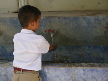 CHOLBURI, THAILAND - August 29, 2013  -  Thai elementary student is washing his hand at the school