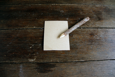 Pencil with a little paper on wood background Stock Photo