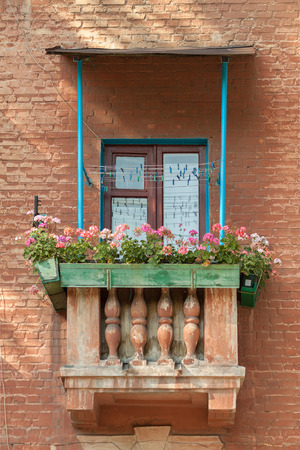 wooden window: Vintage romantic balcony with wooden window frame, lace curtains and balusters in an old house with flowerpot
