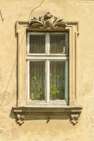 stucco house: A window in an old house. Authentic wooden window frame. Stucco. Vintage wallpaper