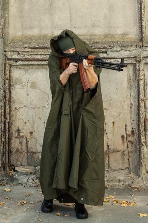 kalashnikov: a man in a military coat and a balaclava aiming a machine gun of Kalashnikov RPK