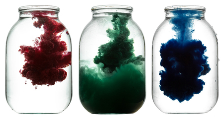 dissolution: RGB paint swirling in water. Splashes of paint in a glass jar.