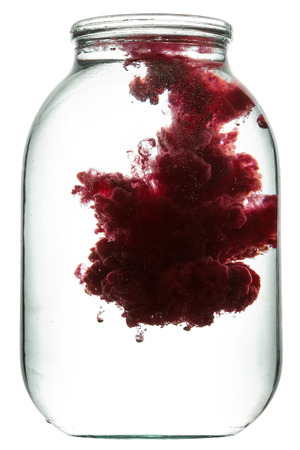swirling: Paint swirling in water. Splashes of paint in a glass jar. Stock Photo