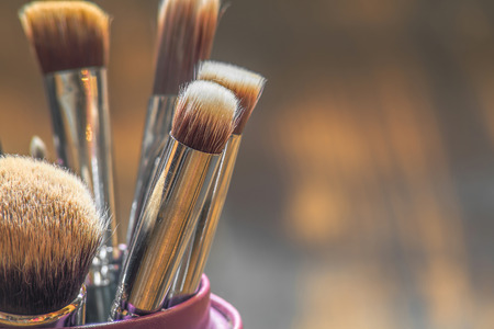make dirty: Professional makeup brushes in tube. Dirty makeup tools. Stock Photo