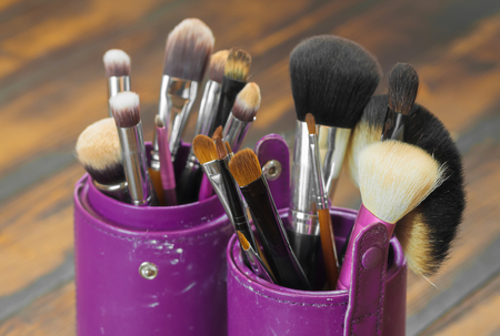 concealing: Professional makeup brushes in tube. Dirty makeup tools. Stock Photo