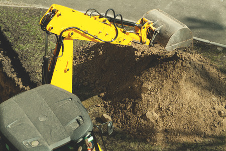trenching: Excavator digs the ground