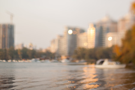 Evening on the autumn beach. Yachts in the bay of the river. Blurry sunset background.