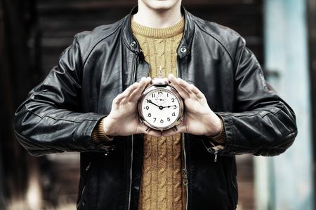 Vintage alarm clock in the hands of man