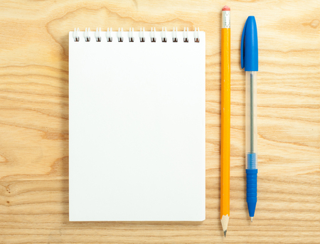 Top view of open spiral blank notebook with pen and pencil on wood desk background