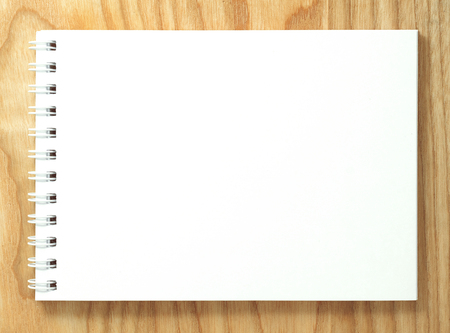 Top view of spiral blank notebook on wood desk background
